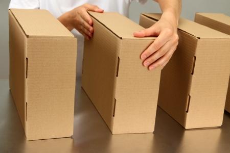 cajas de carton: Trabajador que trabaja con las cajas en la cinta transportadora, sobre fondo gris Foto de archivo