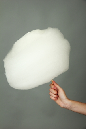 cotton candy: Hand holding stick with cotton candy, on color background Stock Photo