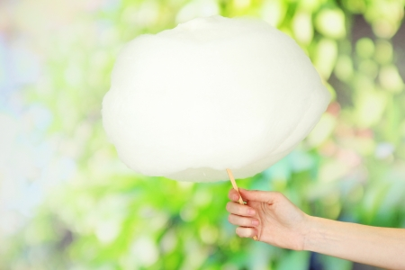 Hand holding stick with cotton candy, on bright background photo