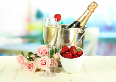 Romantic still life with champagne, strawberry and pink\ roses, on bright background