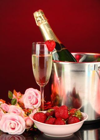 Romantic still life with champagne, strawberry and pink roses, on dark color background photo