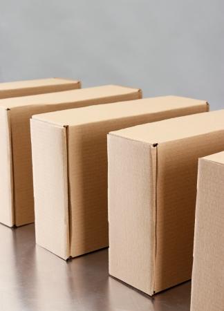 Cardboard boxes on conveyor belt, on grey background photo