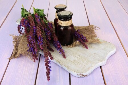 Medicine bottles and salvia flowers on purple wooden background photo