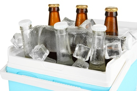 Traveling refrigerator with beer bottles and ice cubes isolated on white photo