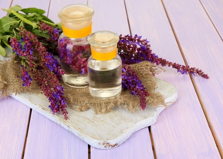 Medicine bottles with salvia flowers on purple wooden background photo