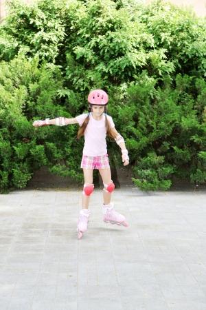 Little girl in roller skates at  park photo