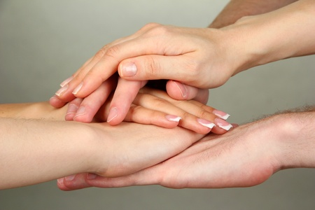 hands joined: Group of young peoples hands on gray background Stock Photo