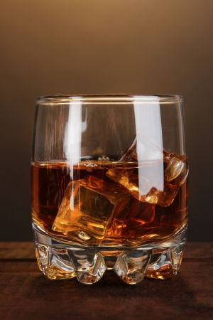 Brandy glass with ice on wooden table on brown background Stock Photo - 20849055