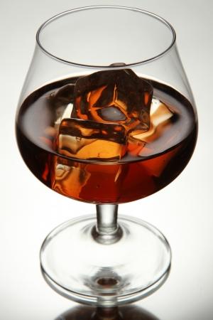 Brandy glass with ice on grey background photo