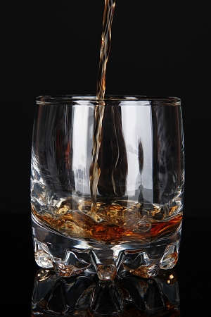 drunks: Brandy pouring into glass on black background Stock Photo