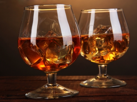 Brandy glasses with ice on wooden table on brown background photo