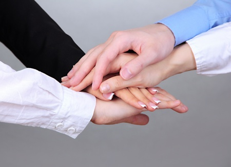Group of young people's hands on gray background photo