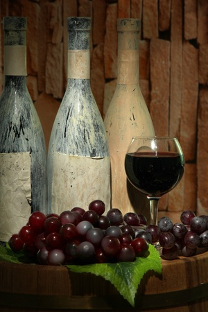 Composition with old bottles of wine and wineglass in old cellar photo