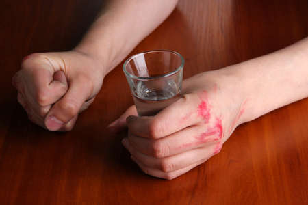 Drunk man hold vodka glass at table close-up photo