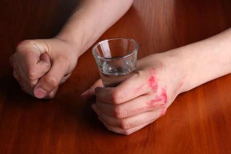 devastation: Drunk man hold vodka glass at table close-up Stock Photo