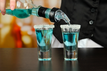 barmen: Barmen hand with bottle  pouring beverage into glasses, on bright background Stock Photo
