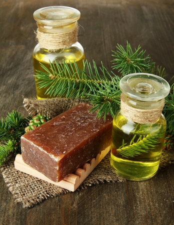 Hand-made soap and bottles of fir tree oil on wooden background photo