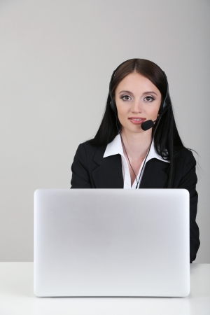Call center operator at work, on gray background photo
