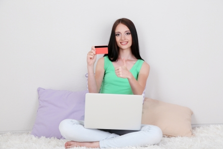 Beautiful young woman sitting on carpet with laptop in room photo