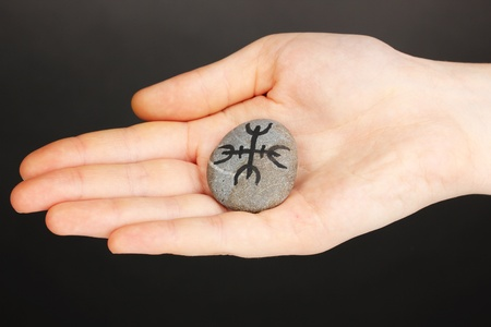 Fortune telling  with symbols on stone in hand on grey background Stock Photo - 20908519