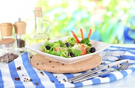 Light salad on plate on napkin on window background photo