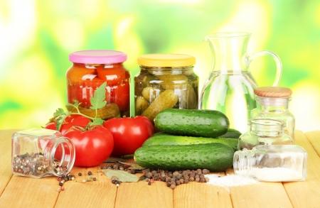 Concombres verts savoureux et les tomates rouges dans le panier, sur la table en bois sur fond clair