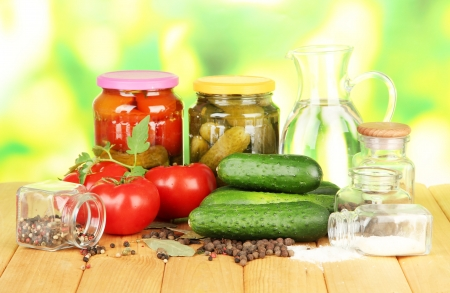 Tasty green cucumbers and red tomatoes in basket, on wooden table on bright  background Stock Photo - 20908147