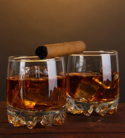 drunks: Brandy glasses with ice and cigar on wooden table on brown background Stock Photo