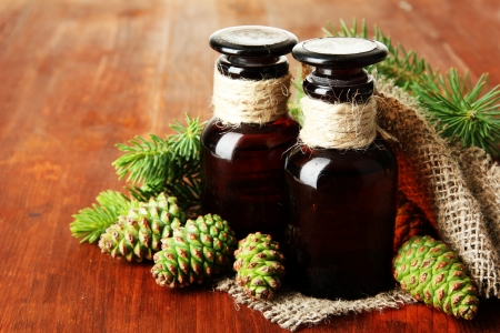 Bottles of fir tree oil and green cones on wooden background photo