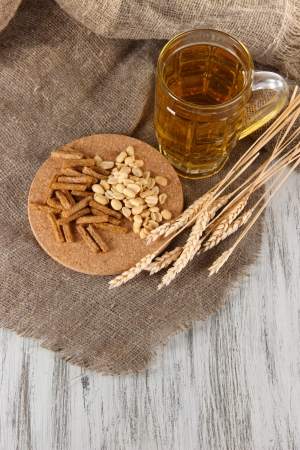 bagging: Beer in glass, crackers and nuts on bagging on wooden table