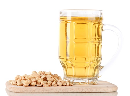 Beer in glass and nuts on on board isolated on white photo