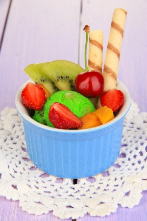 Delicious  ice cream with fruits and berries in bowl on wooden table photo