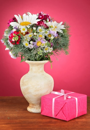 Beautiful bright flowers in vase with gift on table on pink background photo