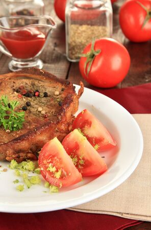 browned: Piece of fried meat on plate on wooden table close-up Stock Photo
