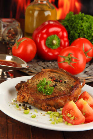 browned: Piece of fried meat on plate on wooden table on fire background