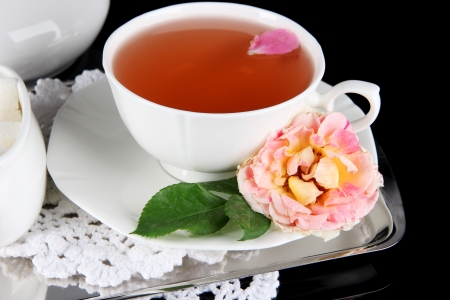 Cup of tea from tea rose on metallic tray on napkin black background photo