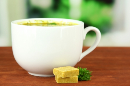 briquettes: Cup of soup with bouillon cubes on wooden table