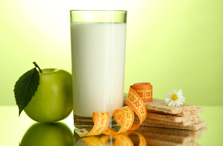Glass of kefir, apple, crispbreads and measuring tape, on green background photo