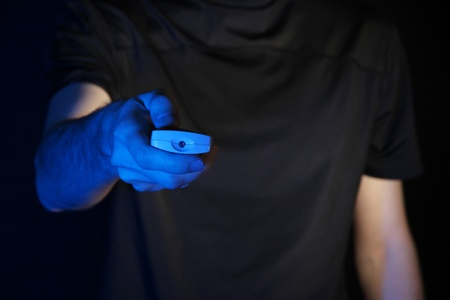 Man hand holding a TV remote control, on dark background photo