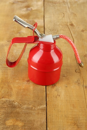 Red oil can, on wooden background Stock Photo - 20962837