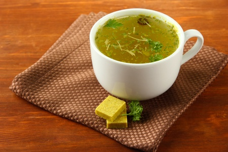 briquettes: Cup of soup with bouillon cubes on wooden background Stock Photo