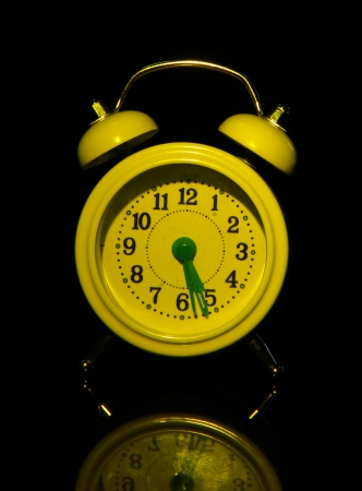 back in an hour: Old style alarm clock isolated on black