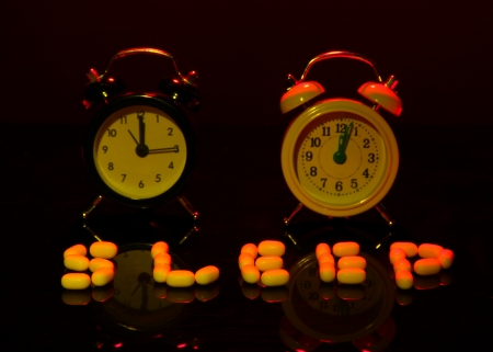 back in an hour: Old style alarm clocks  and pills, on dark background Stock Photo