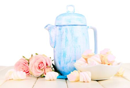 Antique white teapot on wooden table on white background photo