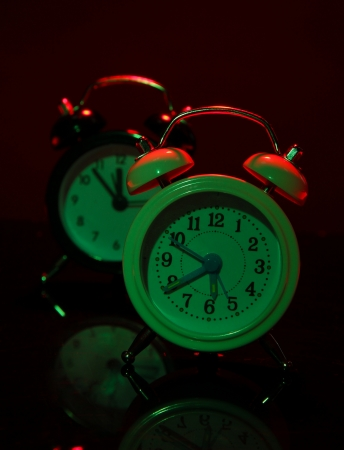 back in an hour: Two old style alarm clocks on dark color background Stock Photo