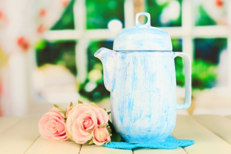 Antique white teapot on wooden table on window background photo