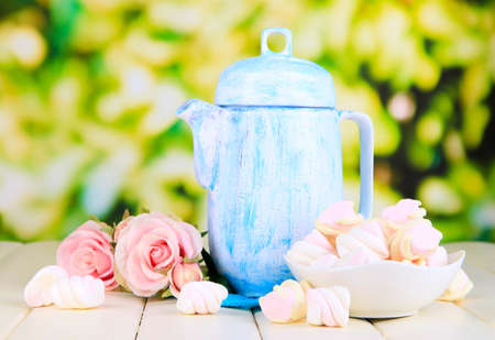 Antique white teapot on wooden table on natural background photo