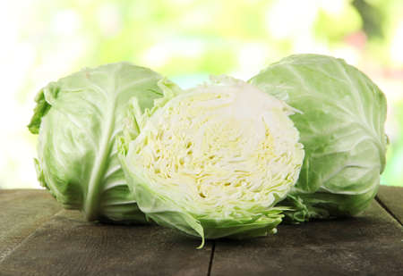 Cabbage on wooden table on nature background