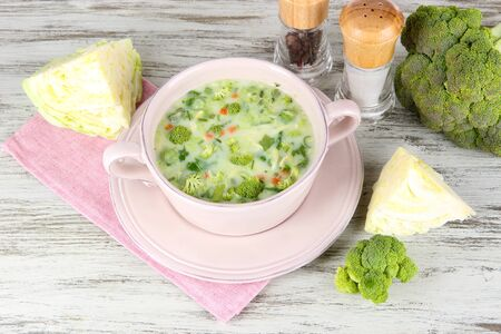 Cabbage soup in plate on napkin on wooden table photo