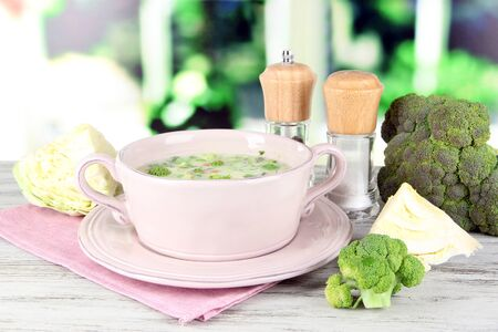Cabbage soup in plate on napkin on wooden table on window background photo